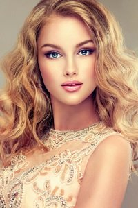 Young beautiful woman, dressed in evening gown. Loose,wavy hair and bright make up.